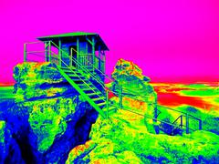 Infrared photo of hut on rock and hilly landscape. Sunny weather. Stock Illustration