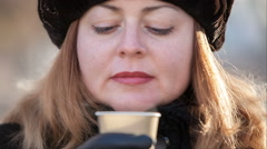 Woman inhales the aroma of hot coffee in the winter - stock footage