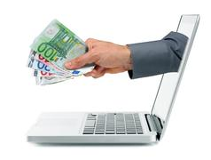 internet earnings concept - hand with money coming out from laptop screen - stock photo
