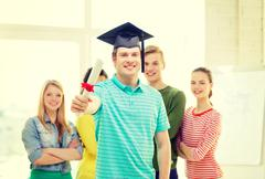 Smiling male student with diploma and corner-cap Stock Photos