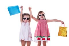 Two happy little girls in sun-glasses and shopping bags Kuvituskuvat
