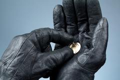 hands with leather gloves holding money - stock photo
