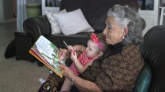 Great grandma reading a book to her granddaughter 02 Stock Footage