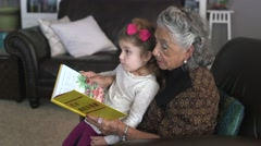 great grandma reading a book to her granddaughter 04 - stock footage