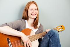 Happy woman with a classical guitar smiling at the camera Kuvituskuvat