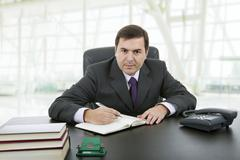 businessman writing on a desk, at the office - stock photo