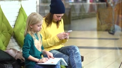 Little blonde girl reading a book while her mom typing a smart phone Stock Footage