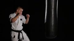 Black belt karate man practicing on the sandbag on black background. Slow motion Stock Footage