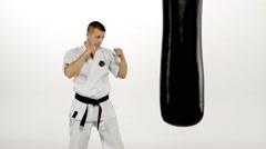 Black belt karate man practicing on the sandbag on white background. Slow motion Stock Footage