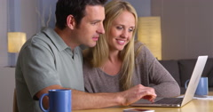 Cute couple looking for vacation getaways on laptop Stock Footage