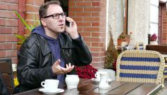 Annoyed man during a conversation on a mobile phone in the cafe - stock footage