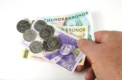 Reaching over swedish money Stock Photos