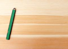Green carpentry pencil on wood - stock photo