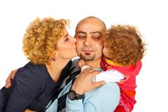 Mom and daughter kissing dad Stock Photos