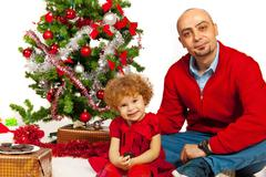 Father and daughter sitting near Xmas tree - stock photo