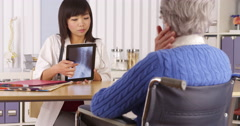 Asian doctor explaining neck x-ray to elderly patient - stock footage