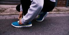 Runner kneels in road and ties shoelaces on shoes Arkistovideo
