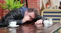 Drunk, overworked, sick or tired man wakes up in outdoor cafe Footage