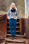 Young cute blonde woman in sweater, scarf, and jeans outdoors portrait - stock photo