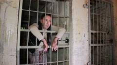 Arrogant looking prisoner behind bars Stock Footage