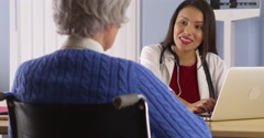 Happy Hispanic doctor talking with senior patient - stock footage