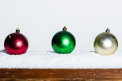 three christmas ornaments on a railing - stock photo
