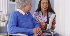 Friendly Mexican caregiver talking to elderly patient with tablet - stock footage