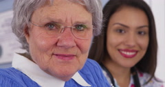 Senior patient and Mexican caregiver looking at camera - stock footage