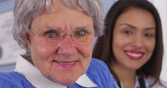 Cheerful elderly patient smiling with Mexican caregiver - stock footage