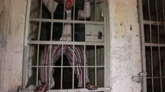 Mad prisioner stands on a cell door. Criminal dance on a prison door. Funny Stock Footage
