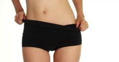Woman slowly removing her black shorts Stock Footage