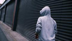 Woman putting on hoodie and starts running in urban area Stock Footage