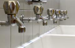 Taps lined up and a white ceramic washbasin Stock Photos