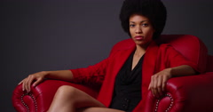 Stock Video Footage of Independent black woman sitting in red chair