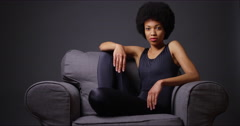African woman sitting in gray armchair Stock Footage