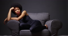 Black woman relaxing on chair looking at camera Stock Footage