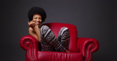 Stock Video Footage of African woman sitting in red armchair