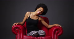 Stock Video Footage of Black woman laughing and moving around  in red leather armchair