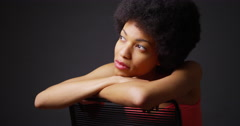Smiling black woman sitting with arms over back of chair - stock footage