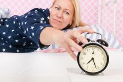 Woman put out the alarm clock Stock Photos