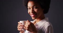 Black woman with afro in studio drinking hot coffee and smiling Stock Footage