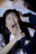 Asian woman screaming while man is abusing and hitting her Stock Photos