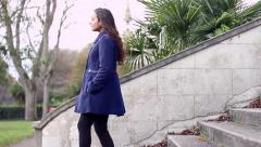Young woman descends stone stairs, tracking shot Stock Footage