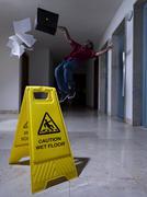 Man slips next to Wet Floor sign Stock Photos