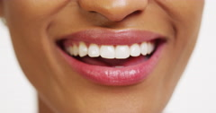 Close up of African woman with white teeth smiling and sticking tongue out - stock footage