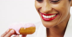 Black woman eating donut with pink frosting and smiling - stock footage