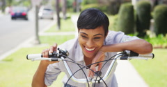 Black woman ringing bicycle bell and smiling outdoors Stock Footage