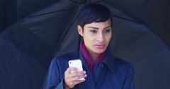 Black woman with umbrella standing in rain using mobile phone - stock footage