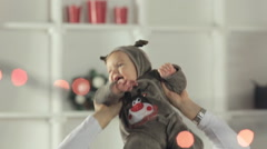 Happy father put his baby in the costume of a deer on the neck and playing with Stock Footage