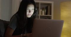 Hispanic woman using laptop at night Stock Footage
